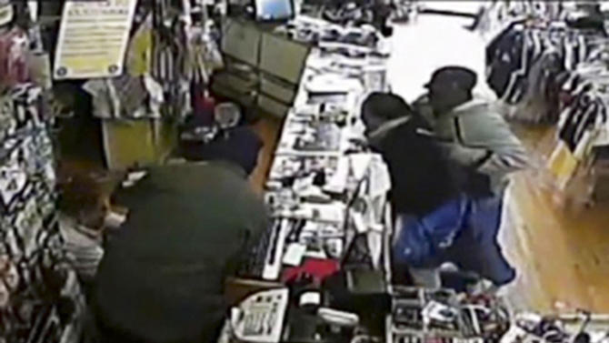 In this image taken from Tuesday, April 9, 2013 surveillance video provided courtesy of Quizhpe Gifts & Fashion, an armed robber, right, holds shop owner Luis Quizhpe's brother-in-law at gunpoint, while another robber, second left, appears to struggle with Quizhpe, on floor at left, during a robbery attempt in Chicago's Logan Square neighborhood. The gunman fired multiple shots at Quizhpe, hitting him in the leg. But the wound failed to stop the shop owner's vigorous counterassault with a baseball bat against the pair of robbers. One man was charged with attempted murder and armed robbery and officers are searching for a second suspect in the incident. (AP Photo/Courtesy Quizhpe Gifts & Fashion)