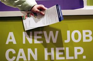 """Man holds pamphlets as he waits at a job fair sponsored by employment website Monster.com as part of their """"Keep America Working"""" tour in New York's Times Square"""