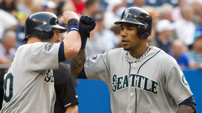 FILE - In this July 19, 2011 file photo, Seattle Mariners' Greg Halman, right, is congratulated by Mike Carp after hitting a three-run home run against the Toronto Blue Jays during the second inning of a baseball game in Toronto. Greg Halman was stabbed to death early Monday, Nov. 21, 2011 in Rotterdam, Netherlands,  and his brother was arrested as a suspect, Dutch police said.  (AP Photo/The Canadian Press, Frank Gunn, File)