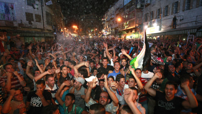 """Palestinians celebrate after Palestinian singer Mohammed Assaf won a regional TV singing contest, in the West Bank city of Ramallah, Saturday, June 22, 2013. Palestinians relished a rare moment of pride and national unity Saturday after the 23-year-old wedding singer from a refugee camp in the Gaza Strip won """"Arab Idol,"""" a regional TV singing contest watched by millions of people. (AP Photo/Majdi Mohammed)"""