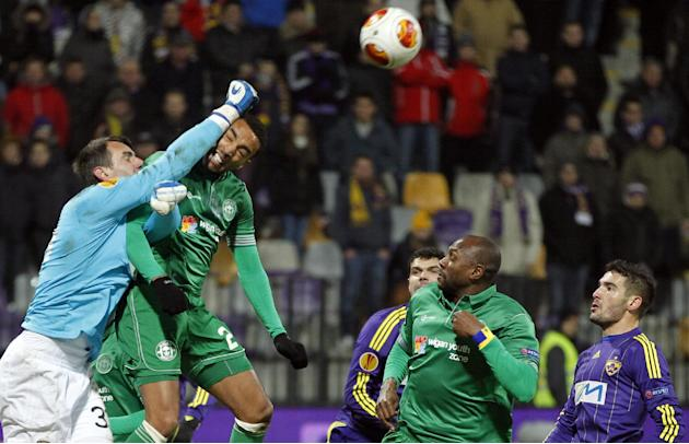 Maribor's goalkeeper Jasmin Handanovic, left, makes a save in front of Wigan's Jean Beausejour, center left, during their group D Europa League soccer match, in Maribor, Slovenia, Thursday, De