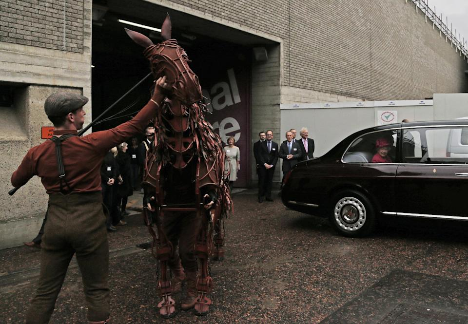 Britain's Queen Elizabeth II, in car, leaves as actors salute using the horse prop from the theatre production 'War Horse' during a visit at the National Theatre in London, Tuesday Oct. 22, 2013 to commemorate the institution's 50th anniversary. (AP Photo/Lefteris Pitarakis, pool)