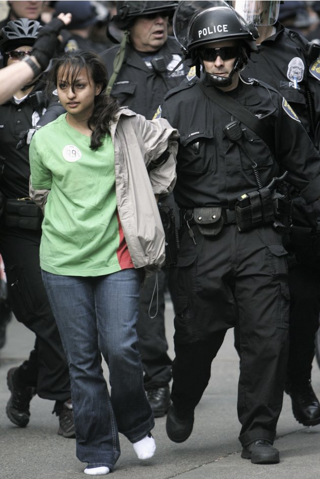 An Occupy Seattle protester is arrested by Seattle police officers during a May Day march and demonstration in downtown Seattle, Washington