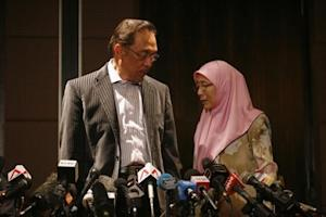 Malaysia's opposition leader Anwar Ibrahim and his wife Wan Azizah Wan Ismail leave after a news conference in Kuala Lumpur