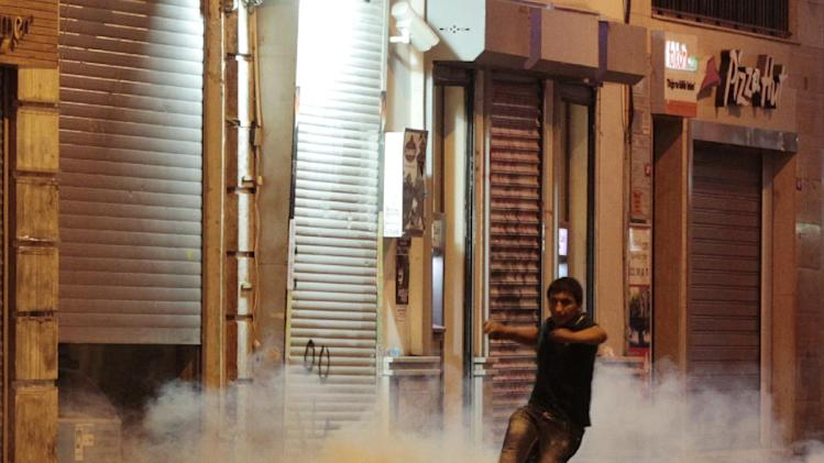 Protester kicks away a tear gas canister during clashes with riot police near Taksim Square in Istanbul, Turkey, Saturday, June 22, 2013. (AP Photo/Petr David Josek)