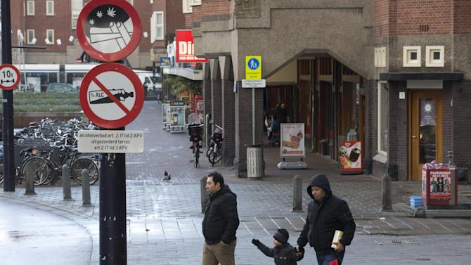 Two men and a child cross a street as a sign prohibiting the use of marijuana in a designated area, top, is seen in Amsterdam, Wednesday Dec. 12, 2012. Amsterdam's mayor Eeberhard van der Laan said Wednesday he would formally ban students from smoking marijuana at school as of Jan. 1, 2013, making the the Dutch capital the first city in the Netherlands to do so. Under the 'tolerance' principle, marijuana is technically illegal here, but police can't prosecute people for possession of small amounts. That's the loophole that made possible Amsterdam's famed 'coffee shops', cafes where marijuana is sold openly.  But it has also had the unwanted side effect that Dutch children are frequently exposed to the drug in public areas. (AP Photo/Peter Dejong)