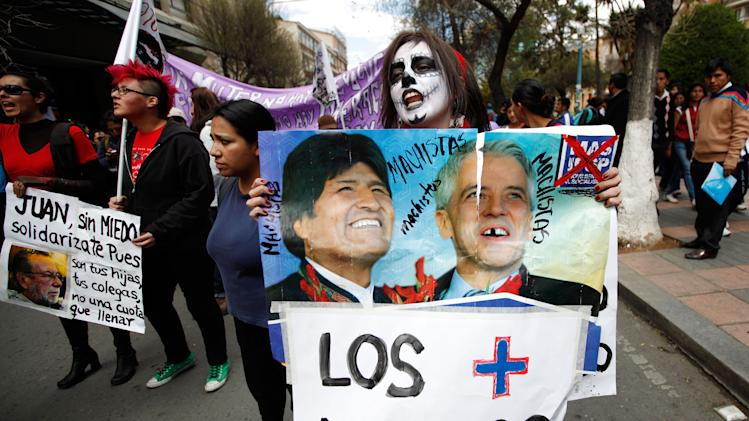 """A women's rights activist shouts slogans and holds a poster showing Bolivia's President Evo Morales, left, and Vice President Alvaro Garcia Linera with the words in Spanish: """"The most machos,"""" a play on words involving their political party's Spanish acronym MAS, which means """"more,"""" at a protest in La Paz, Bolivia, Monday, Sept. 1, 2014. Women's organizations in Bolivia are calling for a """"punishment vote"""" against leading presidential candidates for their alleged sexist attitudes. Morales recently apologized for a senatorial candidate from his party who said on TV that women should be taught to behave so that they're not sexually assaulted. (AP Photo/Juan Karita)"""