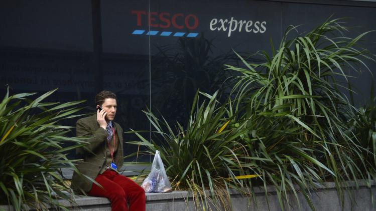 A man sits outside of a branch of the Tesco Express convenience store in London