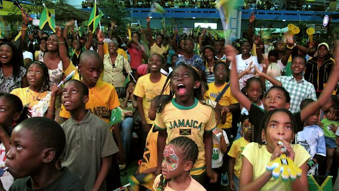 People cheer as they watch Olympic sprinters Usain Bolt and Yohan Blake competing in the 100 m dash at the London Olympics on a large TV screen set up at the national stadium in Kingston, Jamaica, Sunday, Aug. 5, 2012. A crowd of roughly 500 people on the grounds of the national stadium cheered wildly as Bolt crossed the finish line of the 100-meter dash in 9.63 seconds, many dancing and chanting. A group of drummers performed during the meeting. (AP Photo/David McFadden)