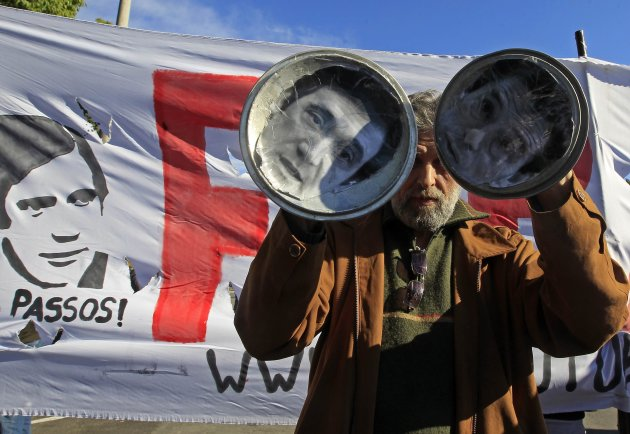 A man holds up pan covers with pictures of Portuguese PM Coelho and Finance Minister Gaspar, during a protest against austerity in front of the presidential palace in Lisbon