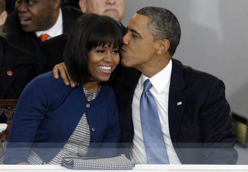 President Barack Obama kisses first lady Michelle Obama in the presidential box near the White House as bands march past the presidential box, Monday, Jan. 21, 2013, in Washington. Thousands  marched during the 57th Presidential Inauguration parade after the ceremonial swearing-in of President Barack Obama. (AP Photo/Gerald Herbert)