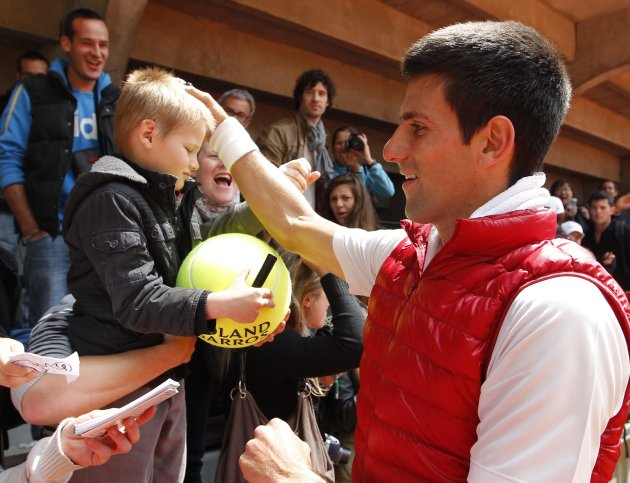 Djokovic of Serbia signs autographs after a training session for the French Open tennis tournament at the Roland Garros stadium in Paris