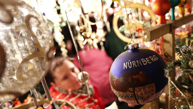 Woman looks at Christmas decorations at opening day of Germany's oldest Christkindlesmarkt in Nuremberg