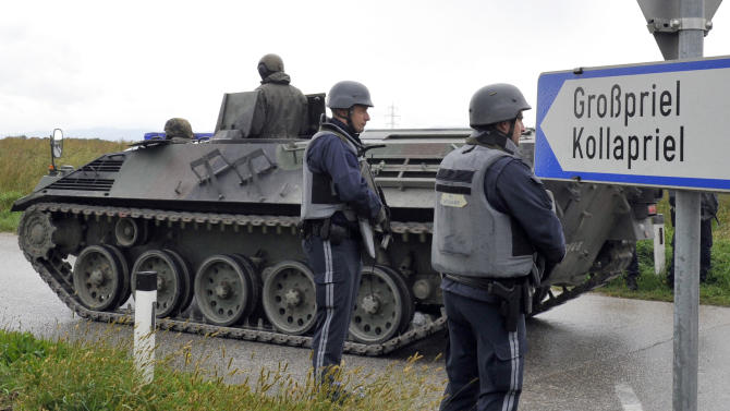 Austrian army soldiers in an armored vehicle arrive near the villages of Grosspriel and Kollapriel some 90 kilometers (55 miles) west of Vienna, Austria, Tuesday, Sept. 17, 2013, where a man is barricading himself inside a farm building after he killed two police officers and the driver of an emergency rescue vehicle as the dpa news agency said, citing an unidentified police spokesman. Interior Minister spokesman Karl-Heinz Grundboeck said a third police officer was apparently being held by the shooter in the village of Kollapriel. He confirmed that three people were shot but refused to say whether their injuries were fatal, explaining that officials did not want to give the gunman information through news reports he was likely monitoring. (AP Photo/Hans Punz)