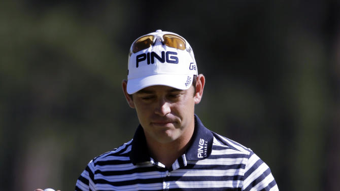 Louis Oosthuizen, of South Africa, holds up his ball after a birdie putt on the eighth hole during the third round of the Masters golf tournament Saturday, April 7, 2012, in Augusta, Ga. (AP Photo/Darron Cummings)