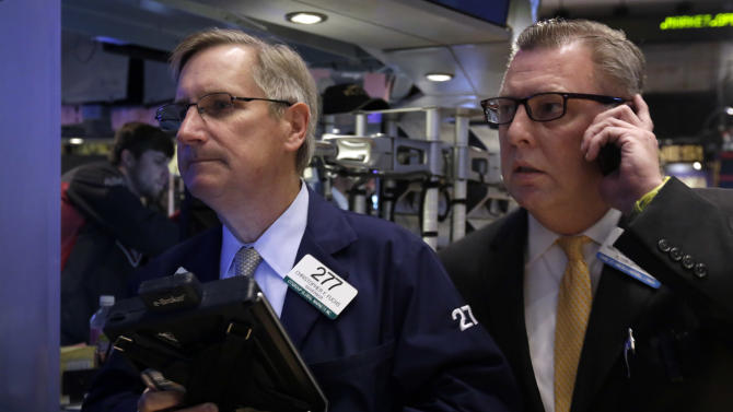 In this Tuesday, Dec. 3, 2013, photo, traders Christopher Fuchs, left, and Matthias Roberts work on the floor of the New York Stock Exchange. World stock markets were muted Tuesday, Dec. 10, 2013 as profit taking offset mildly positive economic indicators from China. (AP Photo/Richard Drew)