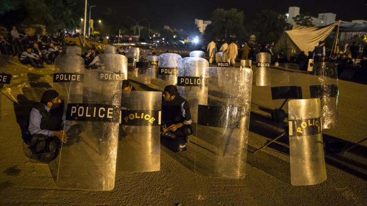"""Police officers sit near their riot shields in front of the Parliament house building during the """"Revolution March"""" protests in Islamabad"""