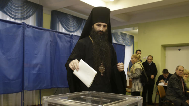 An Orthodox priest casts his ballot paper at a polling station in Kiev, Ukraine, Sunday, Oct. 28, 2012. Voters in Ukraine are choosing a new parliament Sunday. (AP Photo/Efrem Lukatsky)