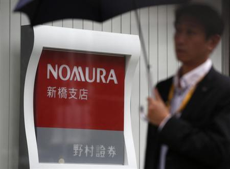 A man holding an umbrella walks past a signboard of Nomura Securities outside its branch in Tokyo