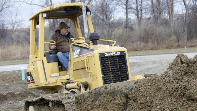 In this Friday, March 28, 2014 photo, Lou Severino moves dirt with a Caterpillar dozer around a home under construction in Pepper Pike, Ohio. Caterpillar reports quarterly financial results on Thursday, Oct. 23, 2014. (AP Photo/Tony Dejak)