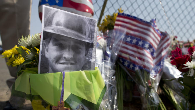 A photo of one of the 19 Granite Mountain Hot Shot crew members who was killed fighting a wild land fire near Yarnell, Ariz. on Sunday, sits at a makeshift memorial outside the crew's fire station, Monday, July 1, 2013 in Prescott, Ariz. An out-of-control blaze overtook the elite group of firefighters trained to battle the fiercest wildfires, killing 19 members as they tried to protect themselves from the flames under fire-resistant shields. The disaster Sunday afternoon all but wiped out the 20-member Hotshot fire crew leaving the city's fire department reeling. (AP Photo/Julie Jacobson)