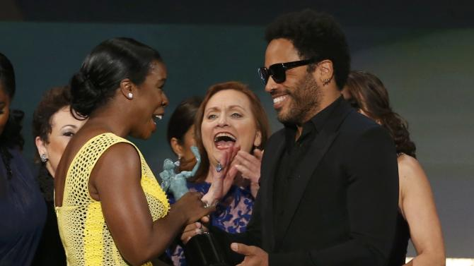 "Uzo Aduba of the Netflix series ""Orange is the New Black"" accepts the award for Outstanding Performance by an Ensemble in a Comedy Series from presenter Lenny Kravitz at the 21st annual Screen Actors Guild Awards in Los Angeles"