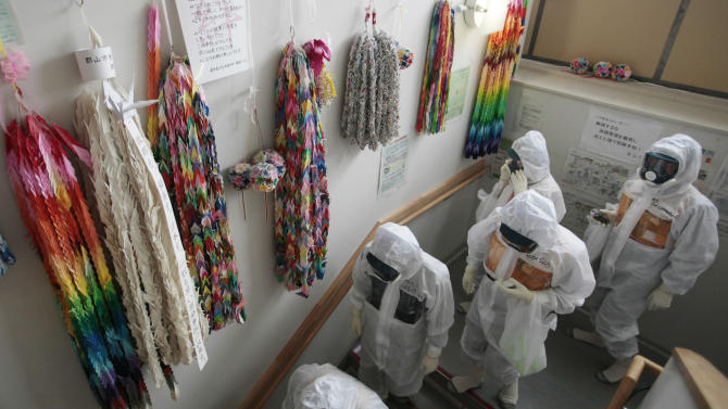 Workers in protective gear walk past thousands paper cranes at the emergency operation center of tsunami-crippled Fukushima Dai-ichi nuclear power plant,  in Okuma in Fukushima prefecture Wednesday, June 12, 2013. More than two years after Japan's nuclear disaster, damaged vehicles, twisted metal and other debris remain strewn about the Fukushima plant. Scores of pipes and hoses cover the ground in some places, either part of the company's makeshift cooling system or left over from the meltdown.  (AP Photo/Noboru Hashimoto, Pool)