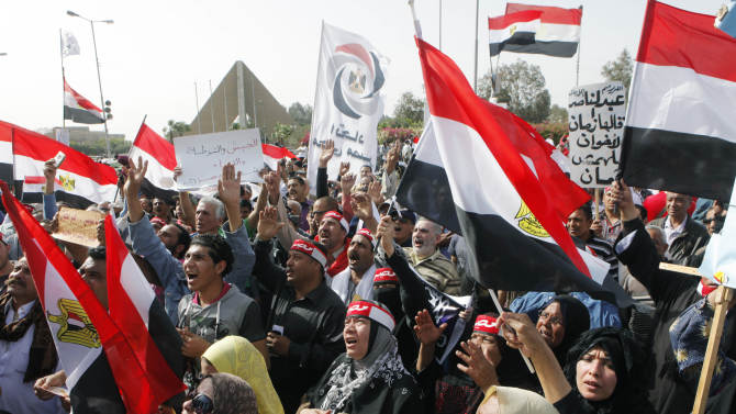 """Supporters of Egypt's military shout anti-Muslim Brotherhood slogans and wave national flags during a protest in front of the Unknown Soldier memorial, in Cairo, Egypt, Friday, March 15, 2013. Hundreds of pro-military supporters gathered to reject the Muslim Brotherhood and President Mohammed Morsi's rule calling for the military to return to power. Arabic on red scarves reads, """"Egypt,"""" and placards in the background read, """"army, police, justice and Egyptian people are one hand,"""" and """"the late president Gamal Abdel Nasser said: don't trust brotherhood."""" (AP Photo/Amr Nabil)"""