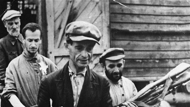 """In this 1941 photo provided by the United States Holocaust Memorial Museum, Jewish men remove looted guns from a barrack in Mogilev, Belarus. Despite all the Holocaust writings, more news is emerging about 1,000 Nazi-run ghettos that left millions of Jews dead. """"Encyclopedia of Camps and Ghettos, 1933-1945, Volume II""""  is a global effort that documents every site of organized Nazi atrocities. (AP Photo/United States Holocaust Memorial Museum) MANDATORY CREDIT: UNITED STATES HOLOCAUST MEMORIAL MUSEUM. ONE TIME USE ONLY, NO ARCHIVING"""