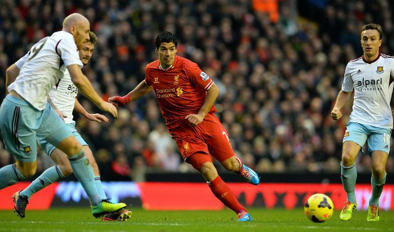 Liverpool's striker Luis Suarez (C) runs with the ball during their English Premier League football match against West Ham United at Anfield in Liverpool on December 7, 2013