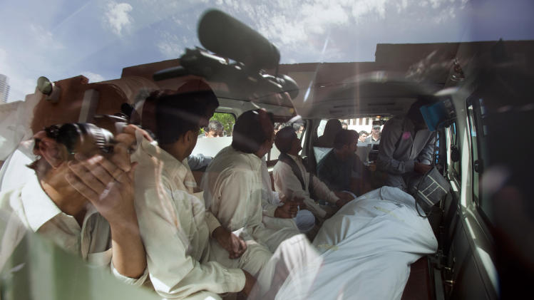 Family members and relatives of slain Pakistani prosecutor Chaudhry Zulfikar sit with his body inside an ambulance at a morgue in Islamabad, Pakistan, Friday, May 3, 2013. Gunmen killed Pakistan's lead prosecutor investigating the assassination of former prime minister Benazir Bhutto as he drove to court in the capital on Friday, throwing the case that also involves former ruler Pervez Musharraf into disarray.(AP Photo/Anjum Naveed)