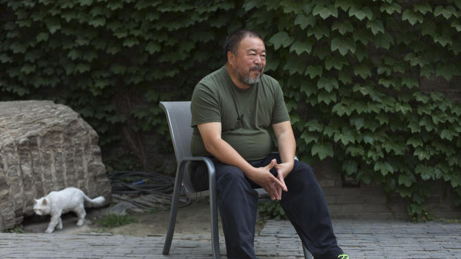 """Artist Ai Weiwei speaks to journalists at the courtyard of his studio in Beijing, China, Wednesday, May 22, 2013. Ai's music video accompanying his heavy metal single """"Dumbass'' released Wednesday depicts an insensitive, overbearing state power that tramples on individual rights. The video is meant to reconstruct his 81-day secret detention in 2011, which was part of the overall crackdown by Chinese authorities on dissent. Ai later was convicted of tax evasion, which his supporters saw as punishment for his activism. (AP Photo/Alexander F. Yuan)"""