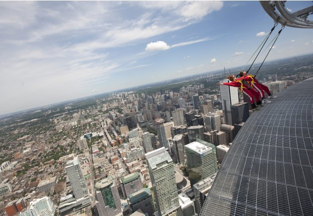 Reporters lean back, 1,168 feet over Toronto's downtown,  while participating in a media preview of the new EdgeWalk attraction on the CN Tower Wednesday, July 27, 2011. Participants are strapped into
