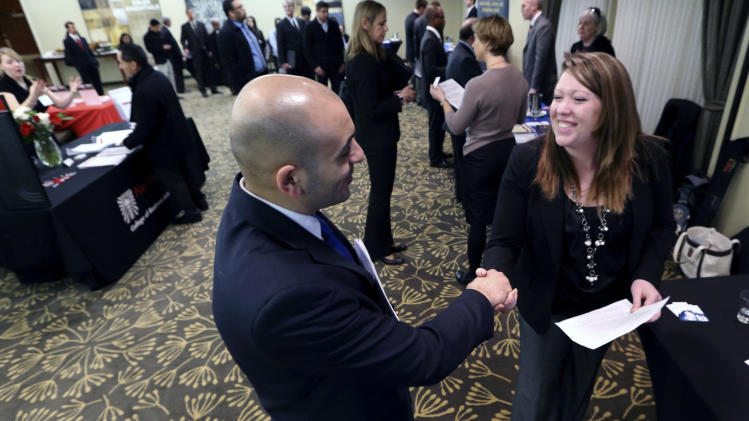 In this Monday, Feb. 25, 2013, photo, Sayed Mouawad, left, of Providence, R.I., shakes hands with Jillian Wallace of Matix, Inc., during a job fair in Boston. The number of people seeking U.S. unemployment aid fell to a seasonally adjusted 340,000 in the week ended March 2, driving down the four-week average to its lowest level in five years. (AP Photo/Michael Dwyer)