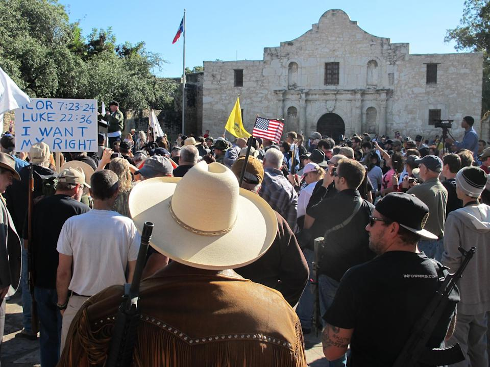 Gun rights advocates gather at the Alamo in San Antonio, Texas on Oct. 19, 2013 to demonstrate in support of a Texas law that permits the open carry of long arms, such as rifles and shotguns. Organizers said a local ordinance restricting the carrying of firearms in public conflicts with state law. (AP Photo/Christopher Sherman)