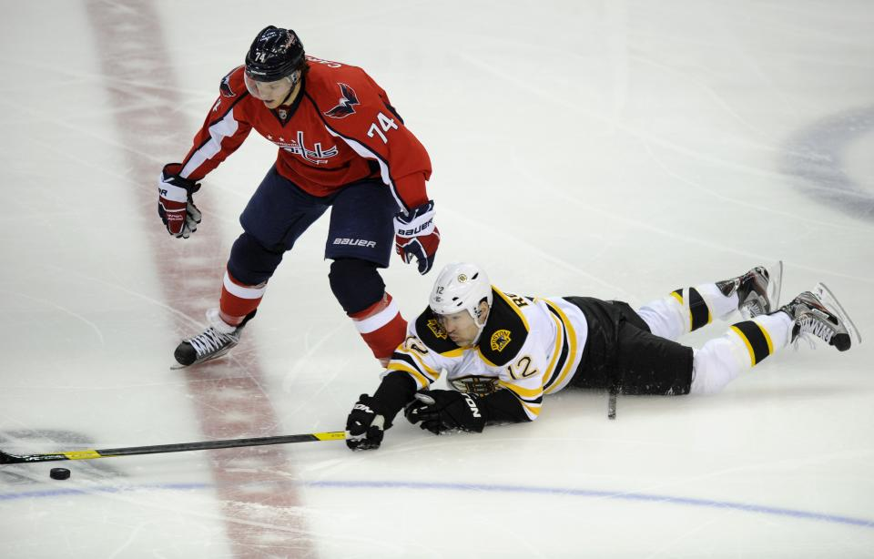 Boston Bruins left wing Brian Rolston (12) reaches for the puck against Washington Capitals defenseman John Carlson (74) during the first period of Game 3 of an NHL hockey Stanley Cup first-round playoff series, Monday, April 16, 2012, in Washington. (AP Photo/Nick Wass)