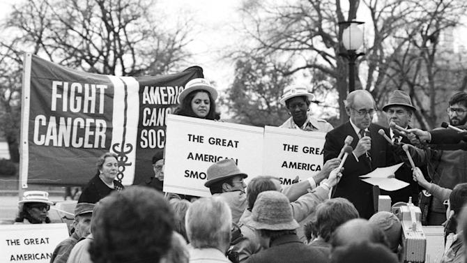 """FILE - In this Nov. 15, 1979 file photo, United States Surgeon General Dr. Julius B. Richmond, at the microphones, kicks off the third annual """"Smokeout"""" rally sponsored by the American Cancer Society in Washington, D.C. as a part of the """"Great American Smokeout Day."""" (AP Photo)"""