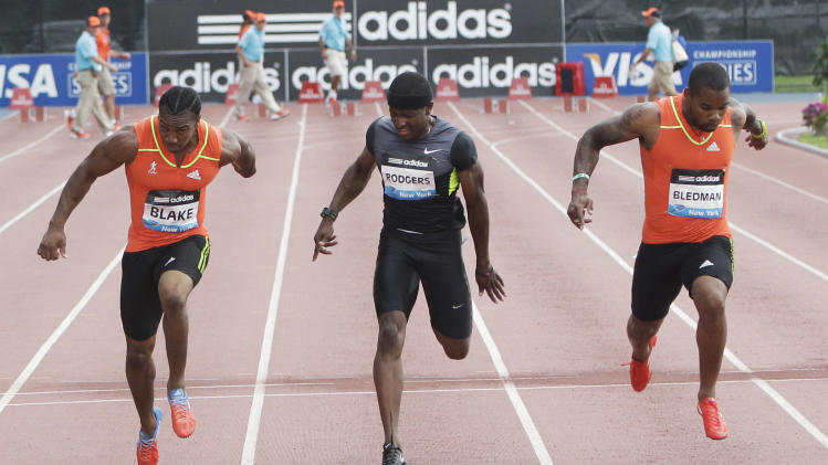 Yohan Blake, left, of Jamaica, wins the men's 100 meters ahead of Michael Rodgers, center, who was third, and Keston Bledman, who took second, at the Adidas Grand Prix track and field meet, Saturday, June 9, 2012, in New York. (AP Photo/Mary Altaffer)