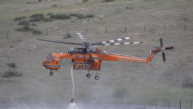 A Erickson Air Crane firefighting helicopter refills its tank in a rancher's pond while fighting  the High Park wildfire west of Fort Collins, Colo., on Friday,  June 15, 2012. The wildfire started Saturday and has burned over 50,000 acres. (AP Photo/Ed Andrieski)
