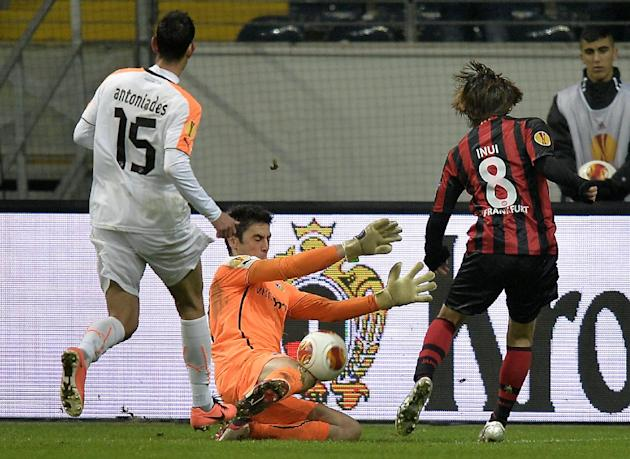 Apoel's keeper Dionisios Chiotis saves a ball from Frankfurt's Takashi Inui of Japan, right,  during the Europa League Group F soccer match between Eintracht Frankfurt and Apoel FC in Frankfur