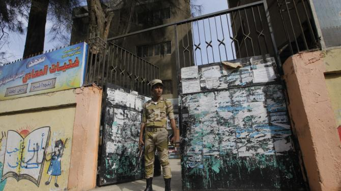 """An Egyptian army soldier stands guard in front of a polling station in Cairo, Egypt, Monday, Jan. 13, 2014. The January 14-15 vote on the draft constitution will be the first real test of the post-Morsi regime. A comfortable """"yes"""" vote and a respectable turnout would be seen as bestowing legitimacy, while undermining the Islamists' argument that Morsi remains the nation's elected president. (AP Photo/Amr Nabil)"""