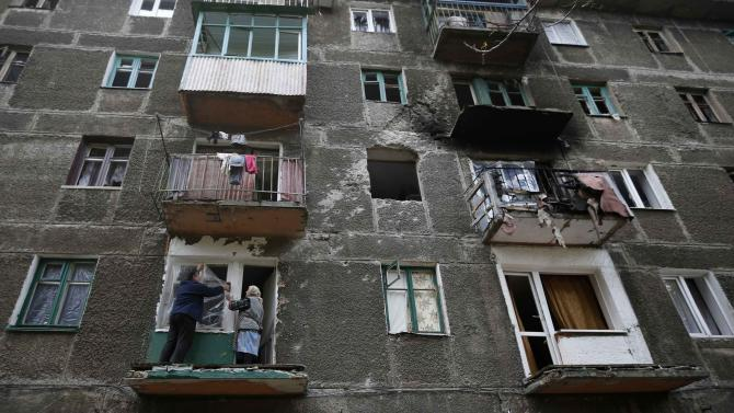 Residents cover a broken window in a building that was damaged during a rocket shelling a day before, in Debaltseve