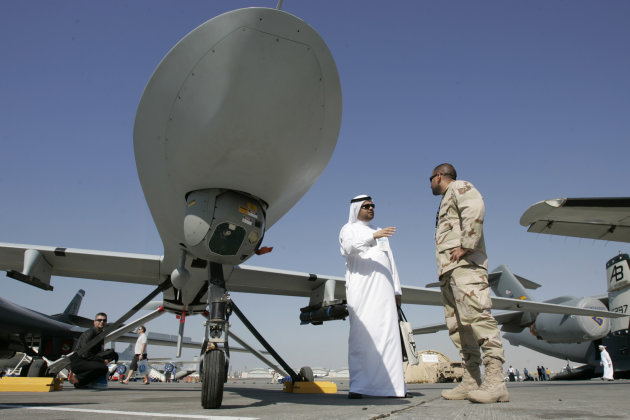 In this Monday Nov. 12, 2007 file photo, an Emarati visitor asks a U.S. military representative questions, as they stand next to an MQ-1 Predator spy plane, during the 2nd day of the 10th Dubai Airshow, at the Dubai airport, United Arab Emirates. In the past two months, the U.S. Defense Department has notified Congress of possible arms deals totaling more than $11.3 billion to Gulf states such as Qatar and Kuwait, which are seen as among the critical frontline partners in U.S. strategies to counter Iran and protect oil shipping lanes. (AP Photo/Kamran Jebreili-File)