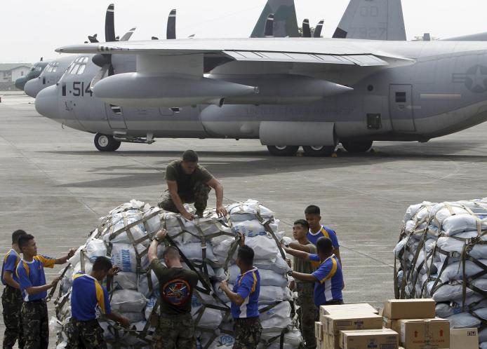 Military personnel prepare to load relief goods on a U.S. C-130 plane at Villamor Air Base