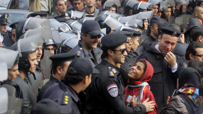 An Egyptian police officer laughs with protesters as he secures a road leading to the Shura Council during a speech by President Mohammed Morsi in Cairo, Egypt, Saturday, Dec. 29, 2012. Egypt's Islamist president warned Saturday against any unrest that could harm the drive to repair the country's battered economy in a sharply worded speech that urged the opposition to work with his government. Mohammed Morsi made the comments in his first speech to the newly convened upper house of parliament, which he said will have full legislative powers until a new lower house of parliament is elected next year.(AP Photo/Amr Nabil)