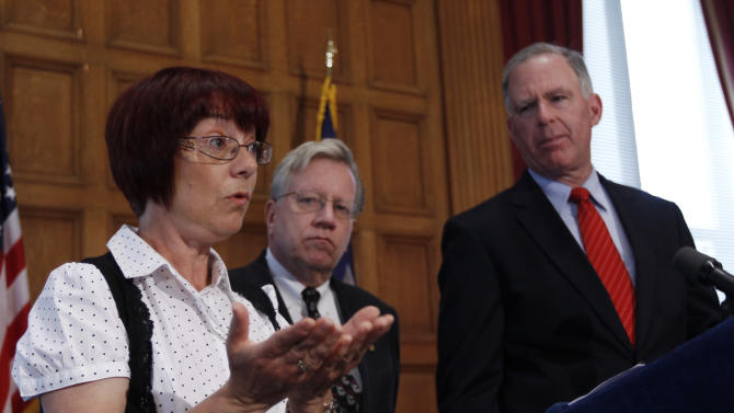 FILE - In this May 14, 2012 file photo, Elaine O'Toole of Tonawanda, N.Y., left, talks about a bill to protect the remains of crime victims during a news conference at the Capitol in Albany, N.Y. Bill sponsors Assemblyman Robin Schimminger, D-Kenmore, center, and Sen. Michael Ranzenhofer, R-Amherst, watch. Gov. Andrew Cuomo and legislative leaders said Monday, June 11, 2012, they have agreed on legislation that would end the power of abusive spouses to dictate what happens to the bodies of the wives or husbands they're accused of killing. (AP Photo/Mike Groll, File)