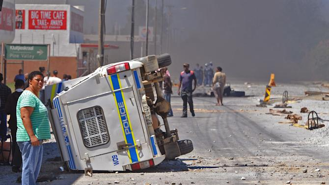A South African Police truck, left, that was overturned by farm workers after they went on a rampage in Wolseley, South Africa, Wednesday, Nov. 14, 2012. Violent protests by farm workers have erupted in South Africa after weeks of unrest in the country's mining industry. Television images showed protesters overturn a police truck and set fires in the streets Wednesday in a town in South Africa's Western Cape. The workers have been protesting their wages, saying they want a minimum wage of $17 a day. Currently, workers make about half that amount a day. (AP Photo)