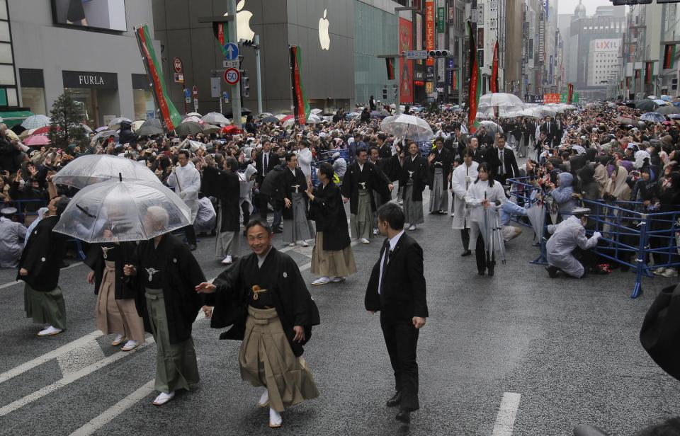 Kabuki actor Shibajyaku Nakamura, second from right, and other actors parade through Ginza shopping district in Tokyo, Wednesday, March 27, 2013.  Some 60 of  kabuki actors paraded Wednesday to newly renovated Tokyo theatre ahead of its official opening. (AP Photo/Shizuo Kambayashi)