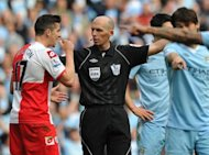 Queens Park Rangers' English midfielder Joey Barton (L) is sent off by referee Mike Dean during the English Premier League football match between Manchester City and Queens Park Rangers at The Etihad stadium in Manchester. Barton apologised for his red card at Manchester City but the controversial QPR midfielder insisted he was only reacting to provocation from Carlos Tevez