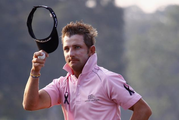 Kruger of South Africa, wearing black ribbons in memory of late Mandela, acknowledges spectators on 18th green after finishing his round during the second day of the European Tour Hong Kong Open golf